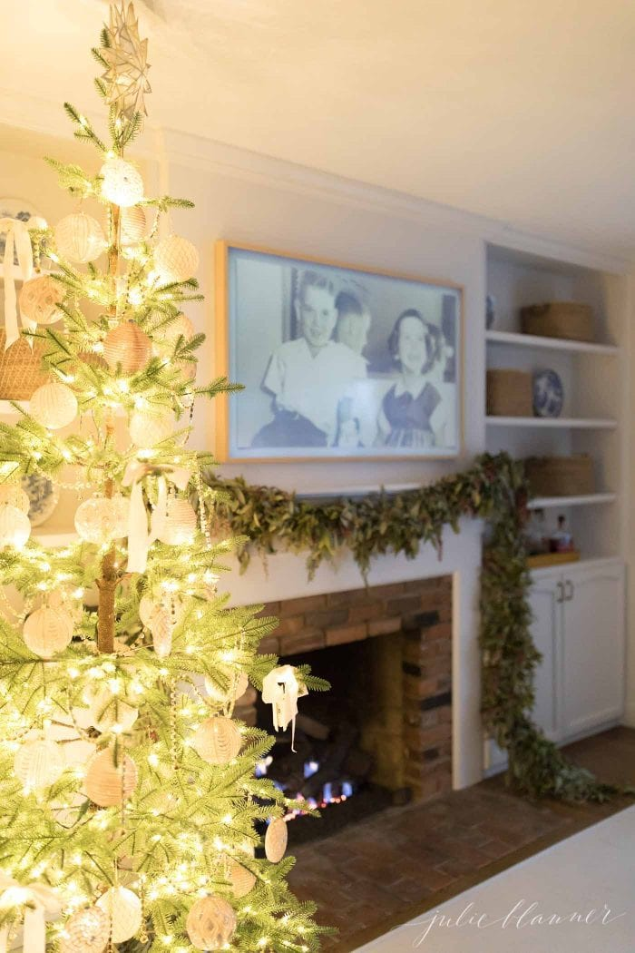 A living room with a christmas tree and garland on a fire place.