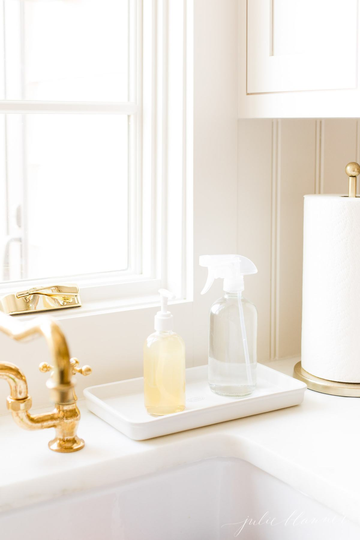 Kitchen Counter Organization soap and cleaning spray on tray next to paper towels