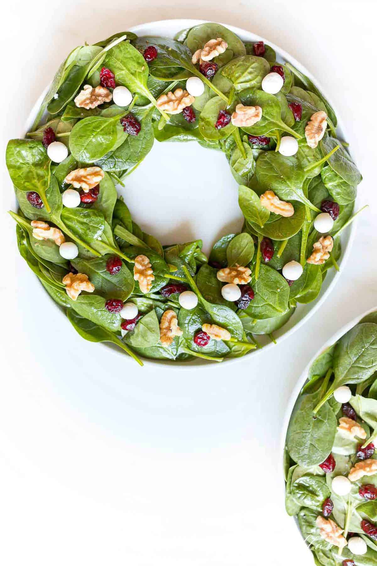 a spinach salad with cranberries goat cheese balls and nuts in the shape of a christmas wreath