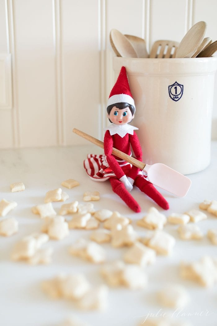 An elf on the shelf next to mini cookies