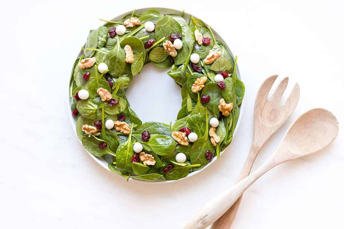 salad in shape of wreath with toppings to look like berries next to wood salad tongs