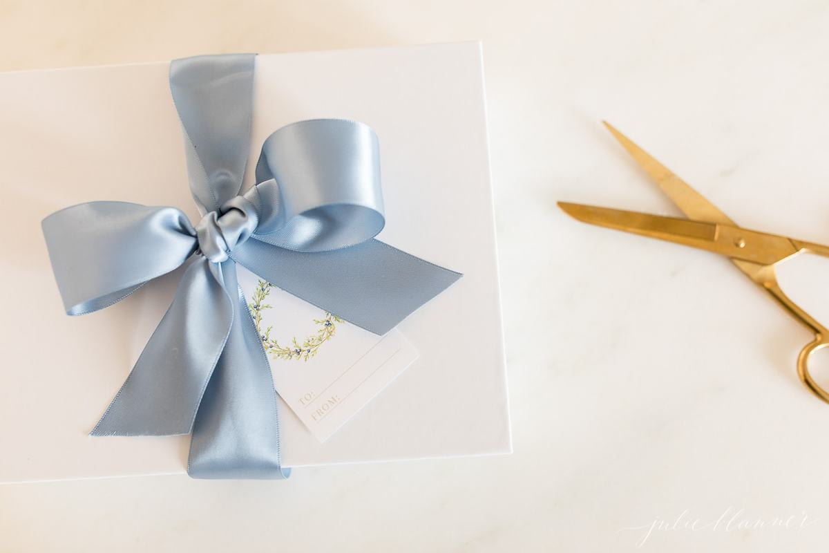free printable christmas gift tags with a green wreath on a white package tied with blue satin ribbon.