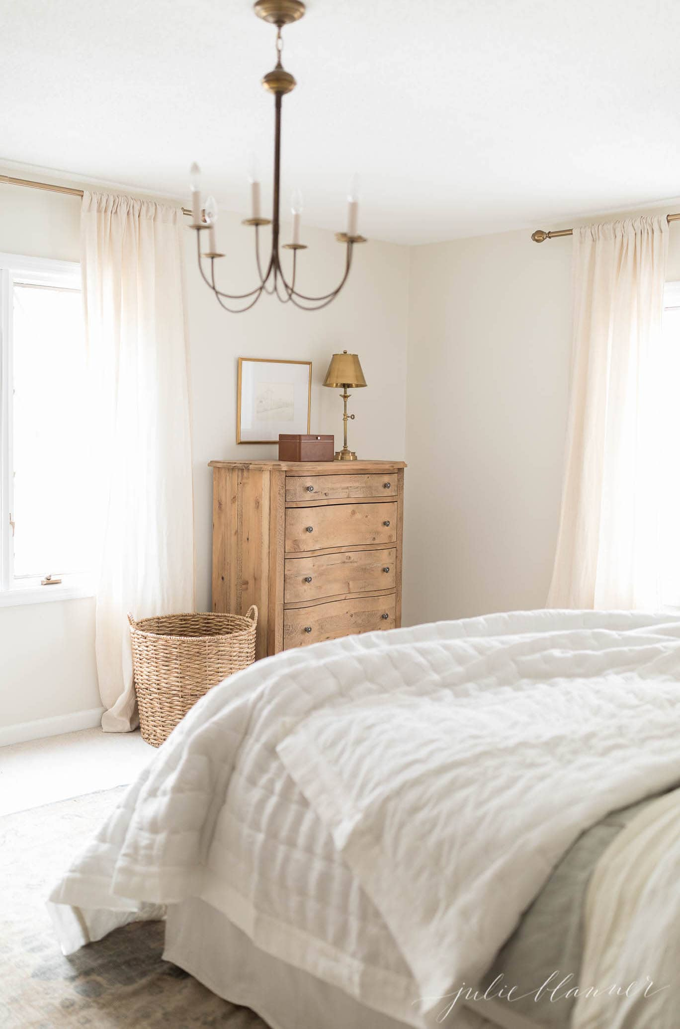 A white bedroom with a large pretty basket for a storage container that doubles as decor.