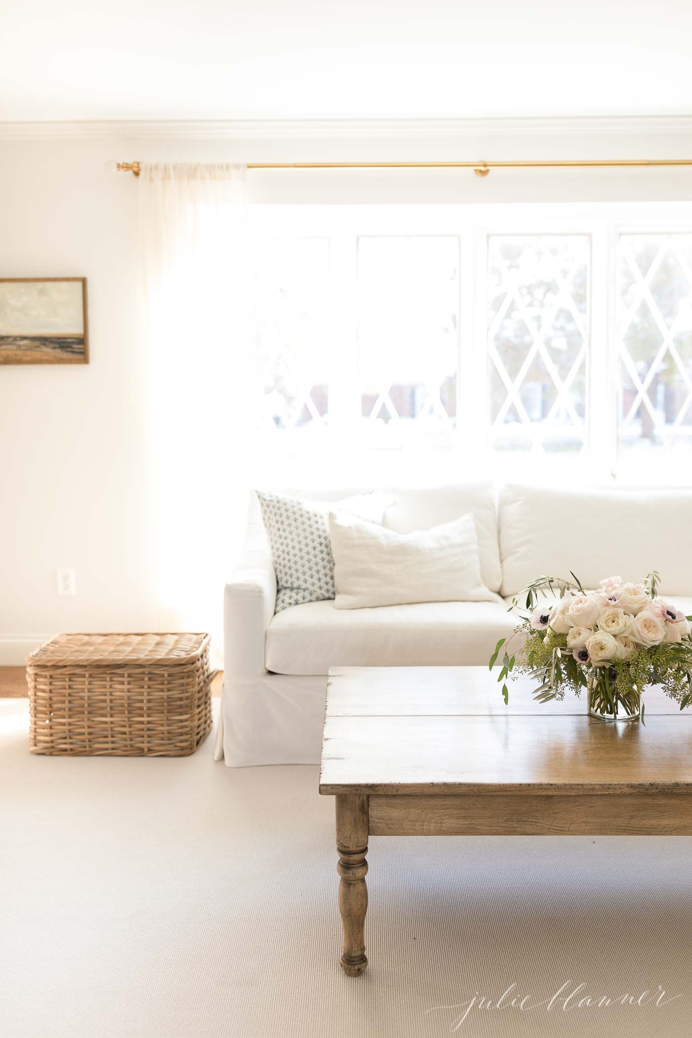A white living room with a pretty basket for a storage container that doubles as a side table.
