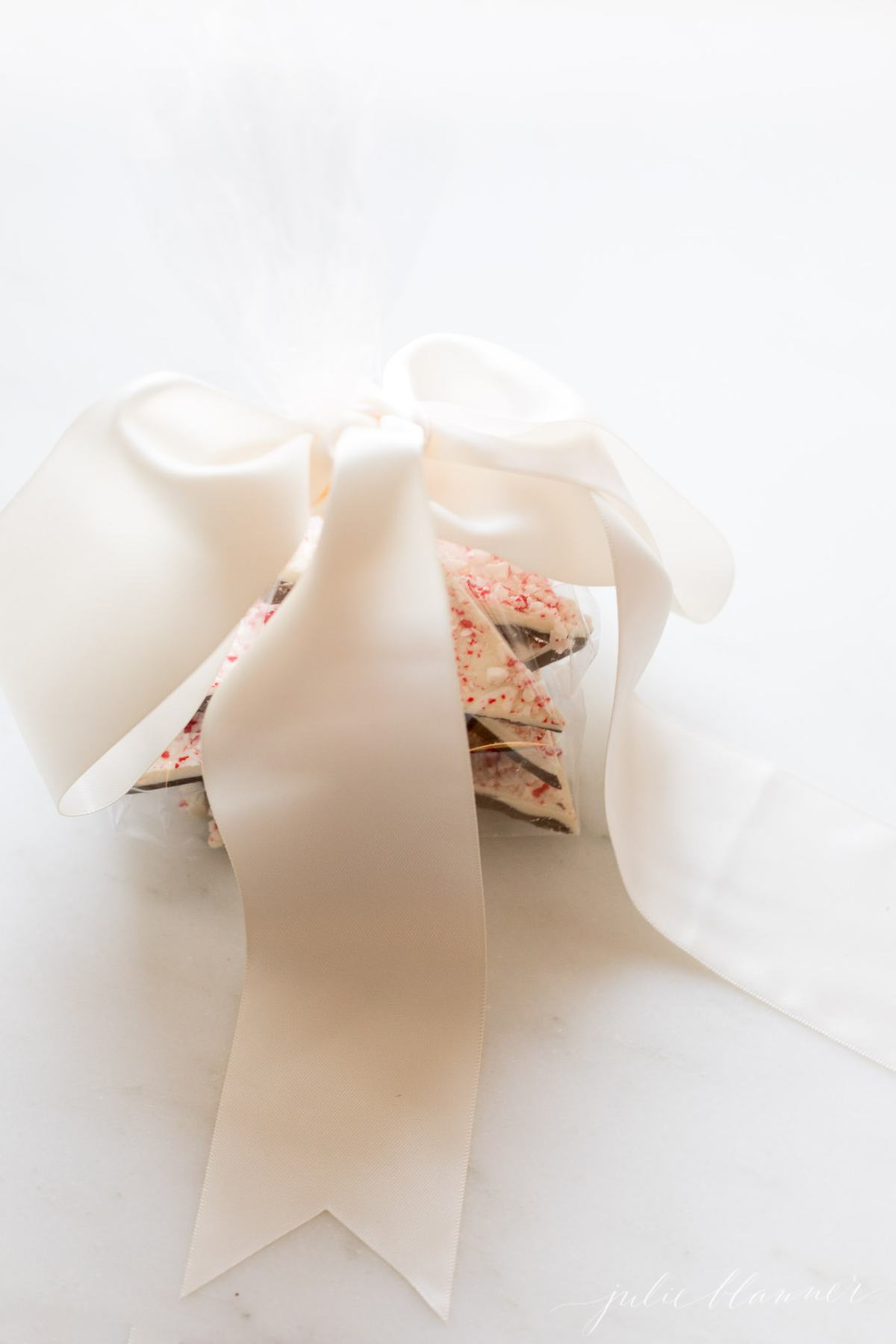 salted peppermint bark gift wrapped with a large bow
