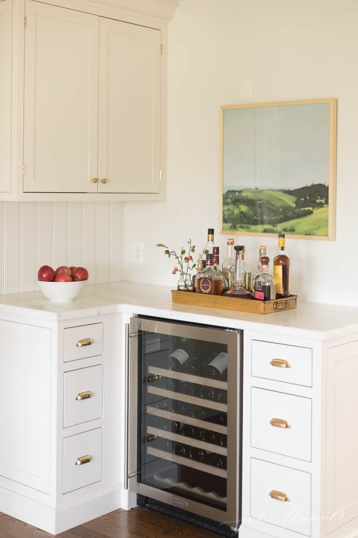 A small bar area in a kitchen with a wine fridge and built in cabinets.