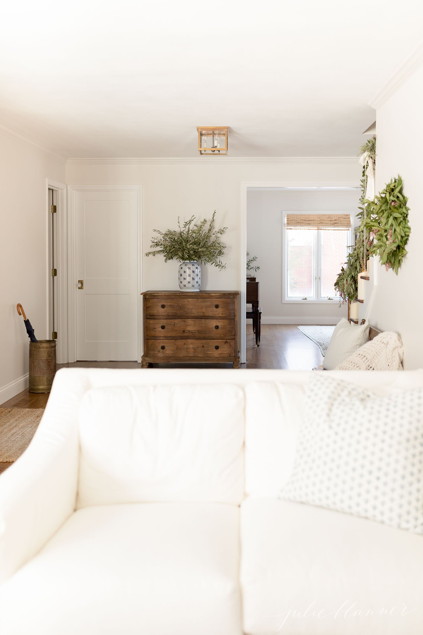 A white living room decorated with holiday greenery and discreet storage containers.