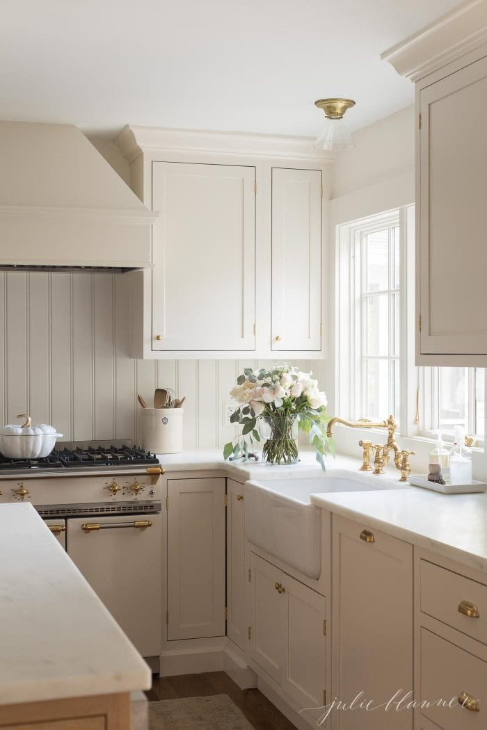 cream cabinets with brass hardware flowers, utensils in a crock and marble counters