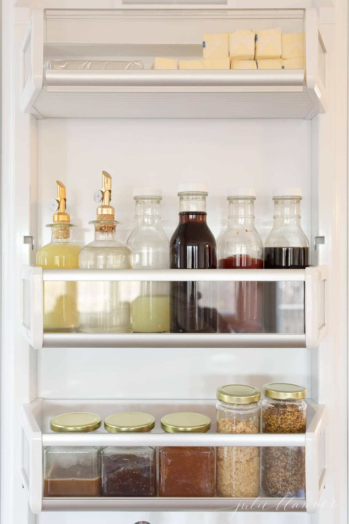 refrigerator organization with clear jars inside a fridge door.