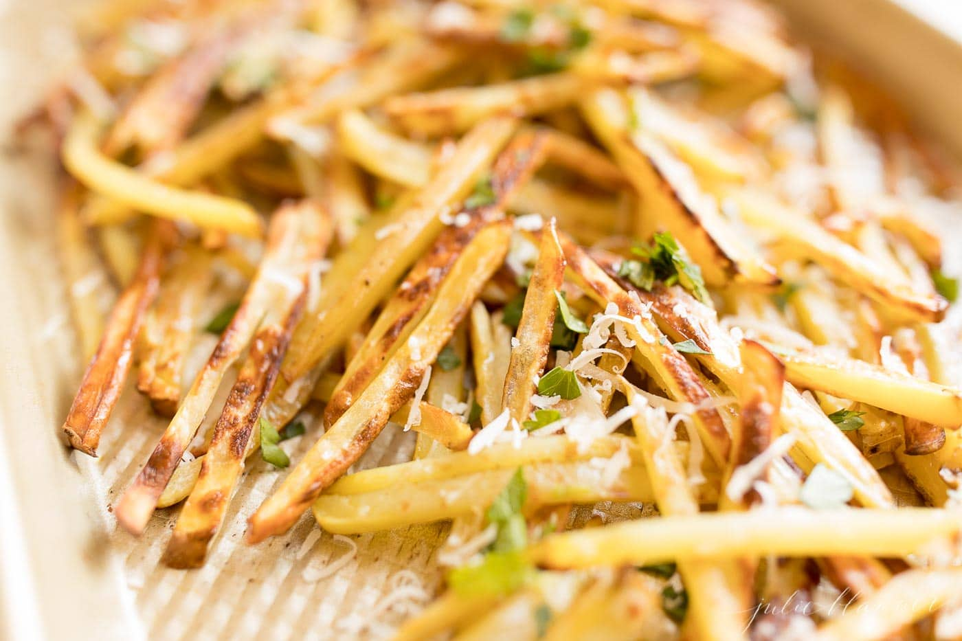 Truffle fries on a sheet pan, topped with parmesan cheese and parsley.