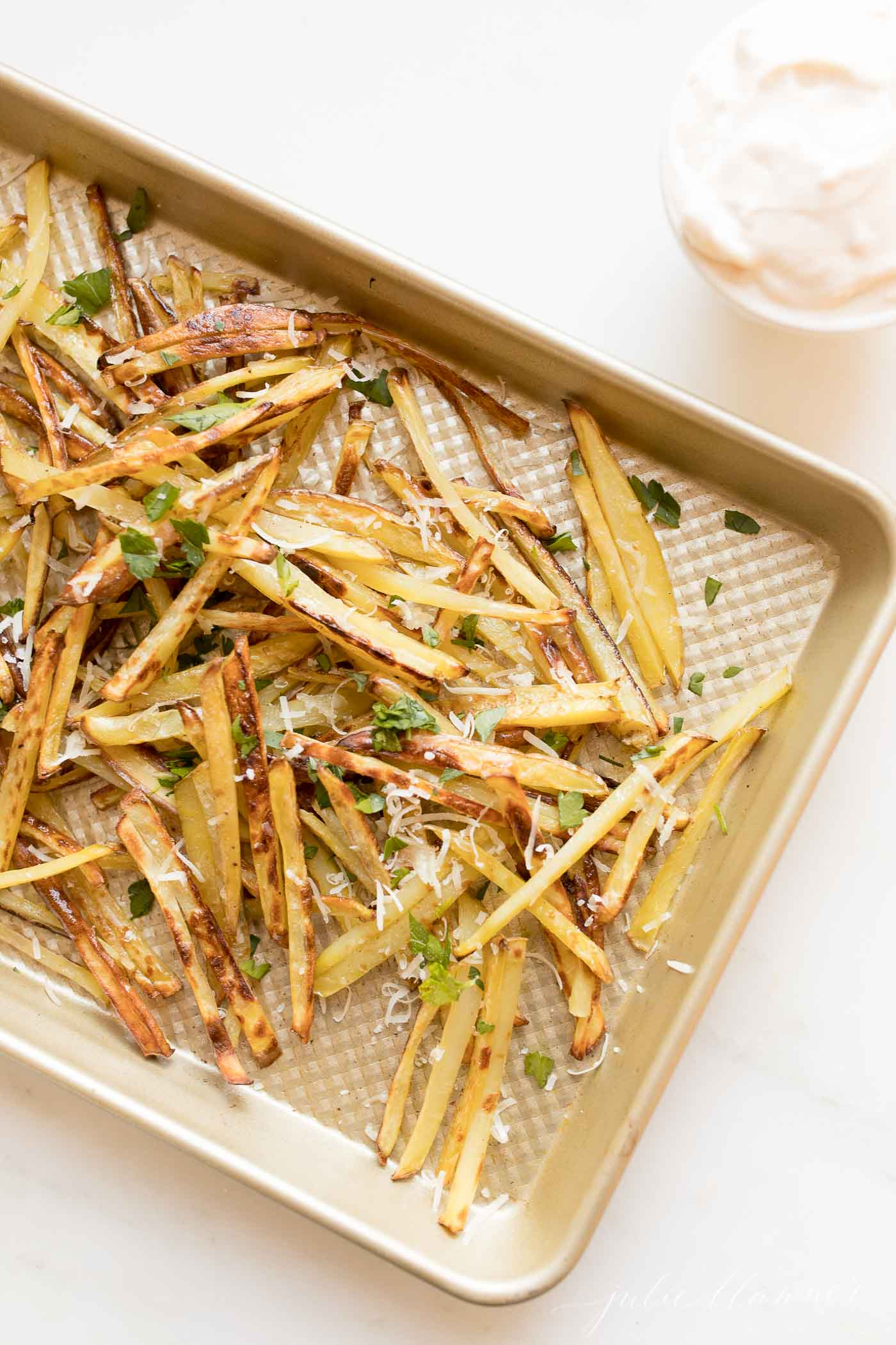Truffle fries on a sheet. pan, topped with parmesan cheese and parsley.