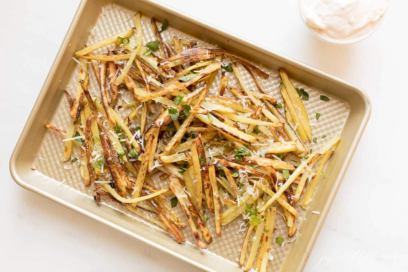 gourmet fries with Parmesan and parsley on a sheet pan