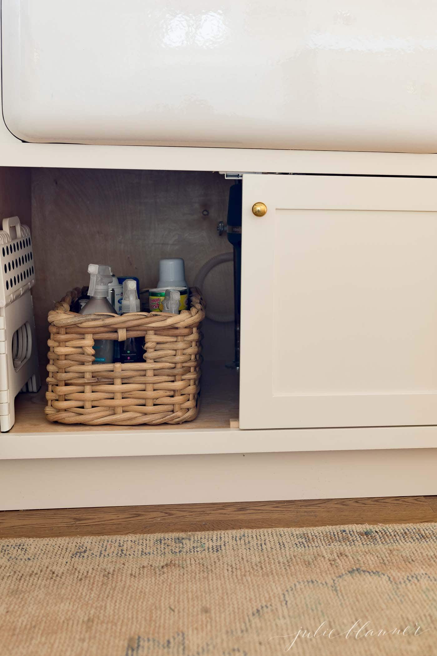 under sink cabinet, one door open to show a basket filled with cleaning supplies.
