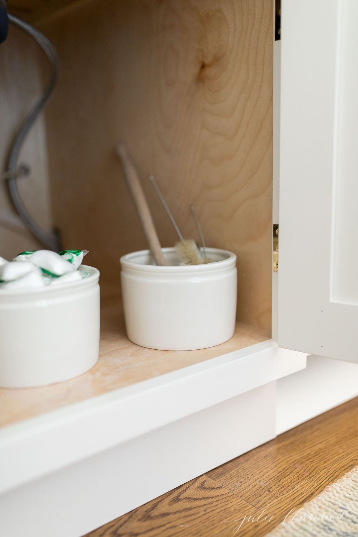 Looking into the cabinet under a kitchen sink, under sink storage ideas like crocks full of cleaning supplies.