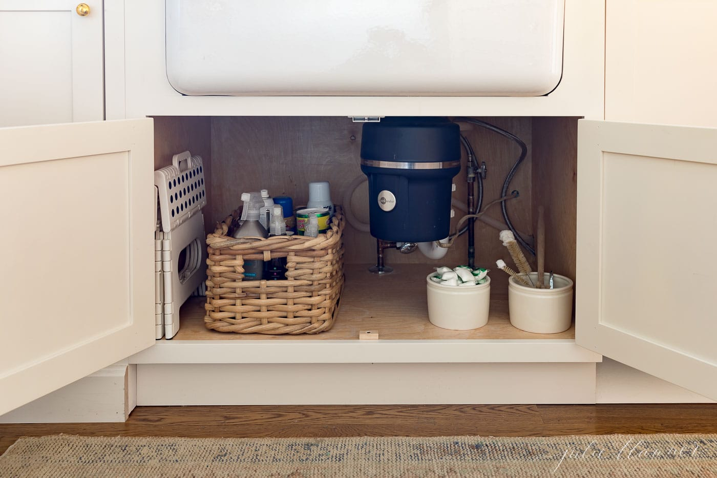 under sink cabinet organized with baskets and tubs.