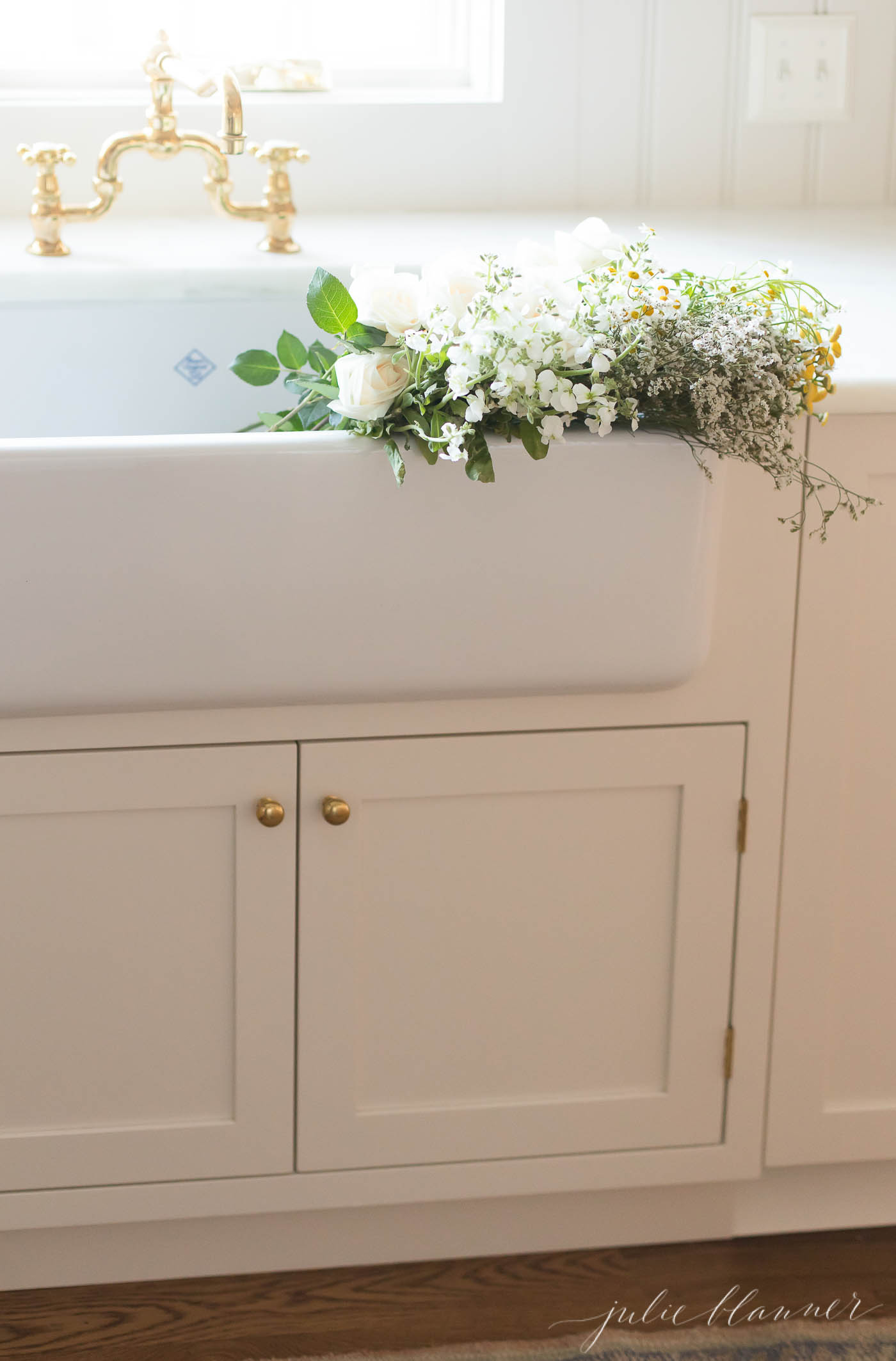 A white farmhouse kitchen sink with a brass faucet and flowers inside.