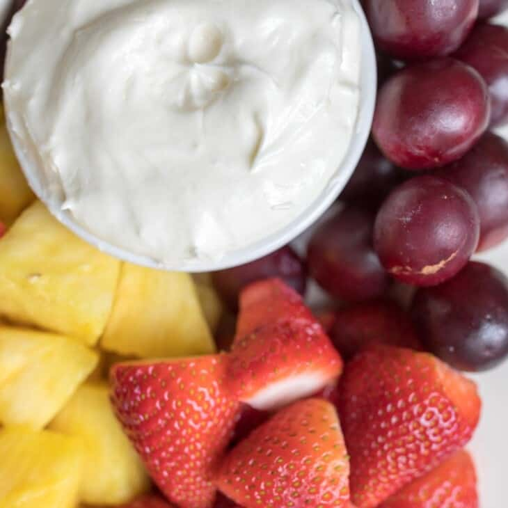 A white bowl full of homemade fruit dip, surrounded by grapes, pineapple and strawberries for dipping.