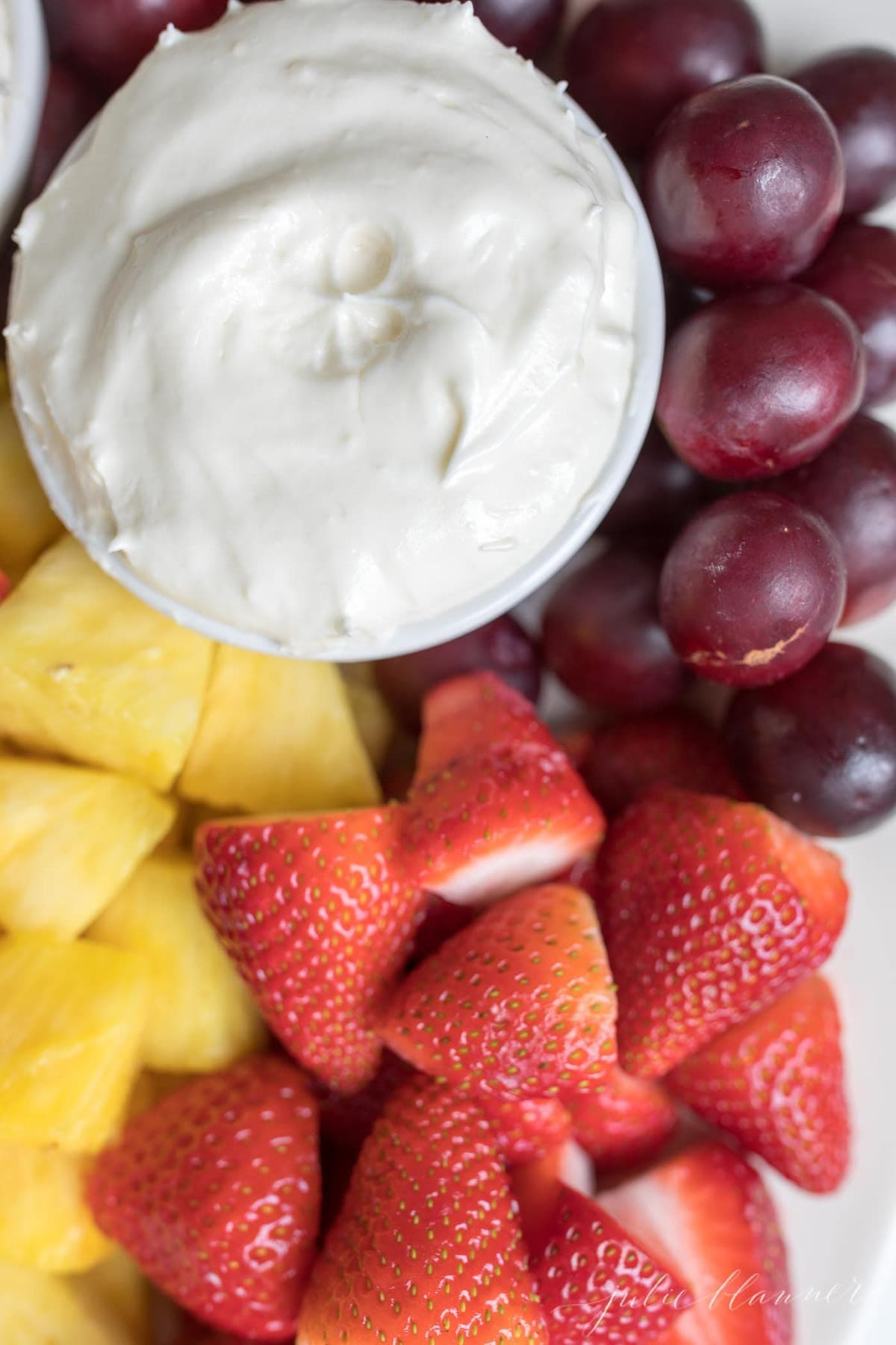 cream cheese fruit dip marshmallow fruit dip in a bowl on a platter of fruit
