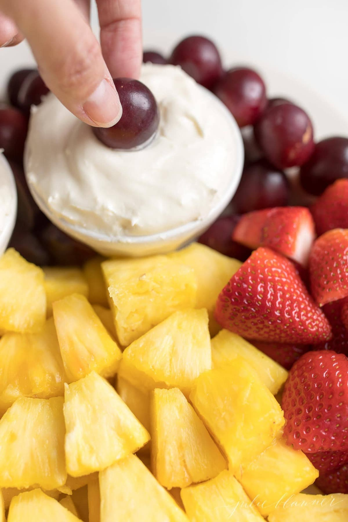 cream cheese fruit dip on a platter of fruit, hand reaching in with a grape to dip.