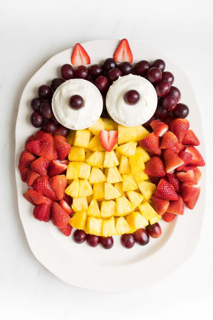 An owl shaped fruit tray, with fruit dip for eyes and strawberries, pineapple, and grapes for the body.