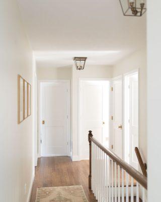 hallway with wood floors brass light