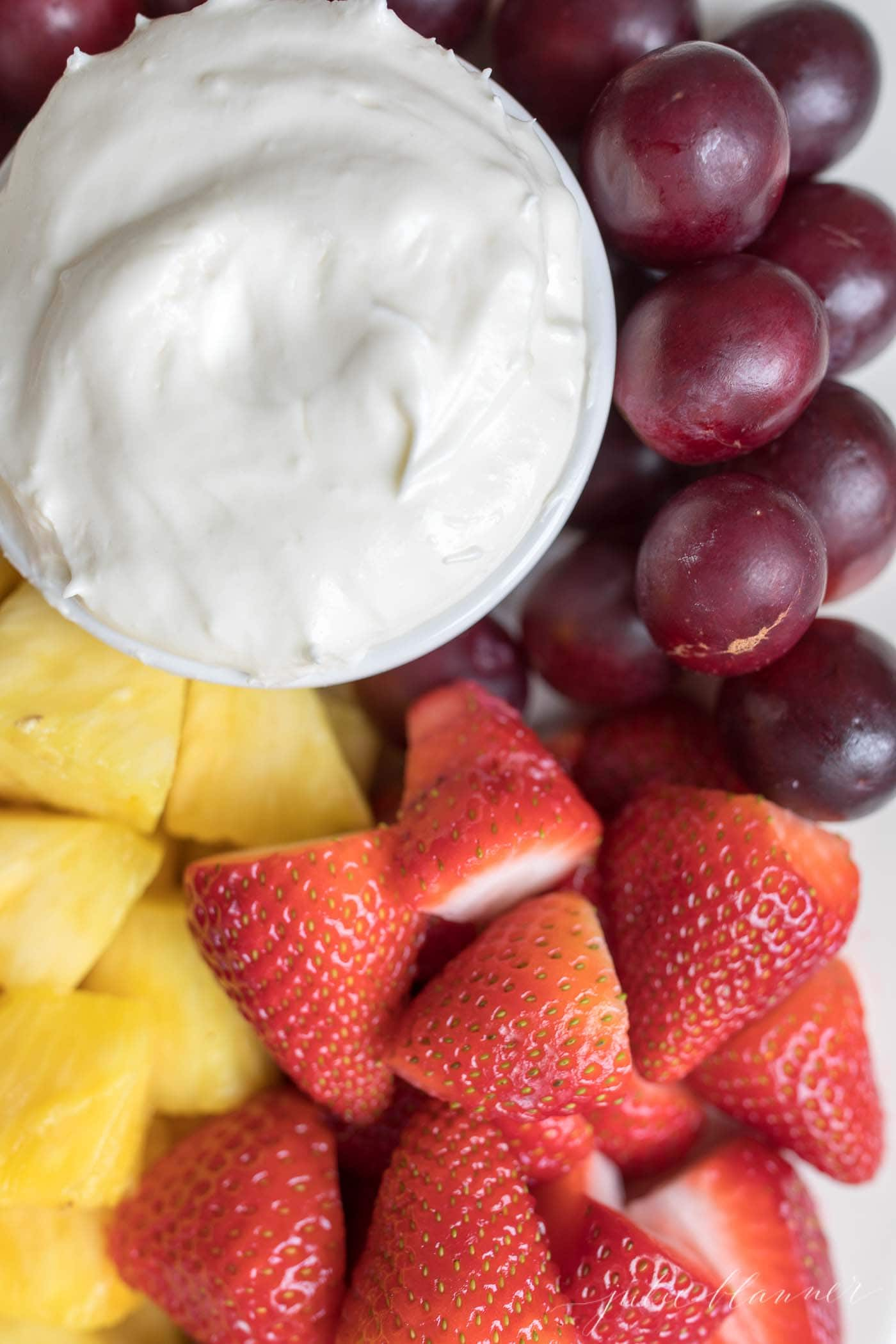 marshmallow fruit dip in a bowl with a platter of fruit