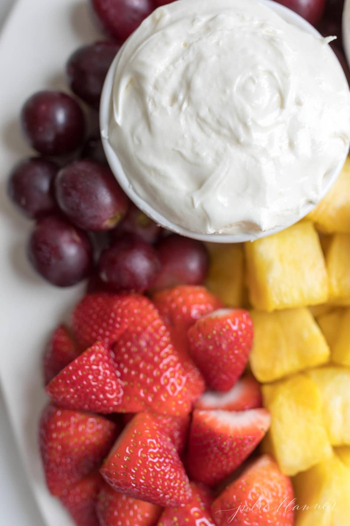 marshmallow and cream cheese fruit dip in a bowl surrounded by fruit