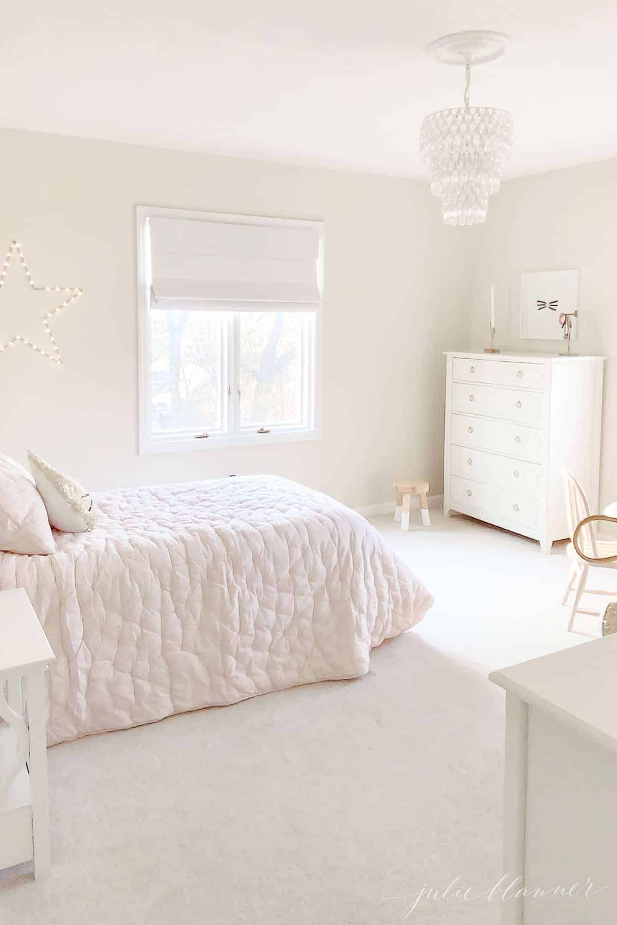pink and cream bedroom with white dresser and crystal light