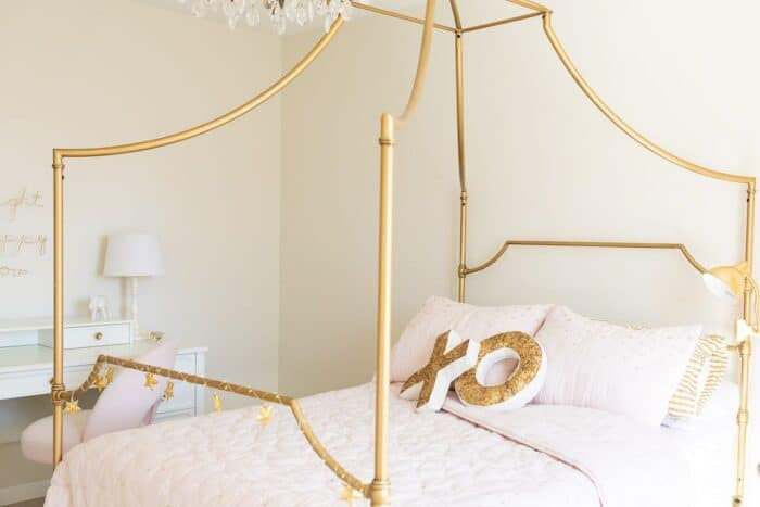 A gold canopy bed with blush pink bedding in a tween girl's room