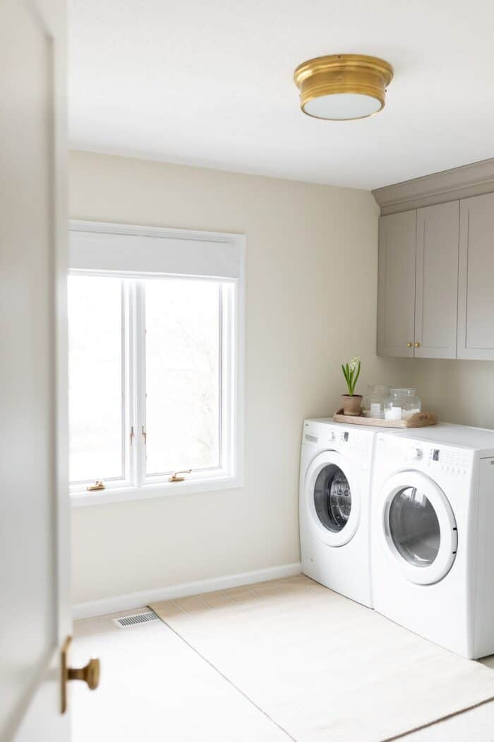 A large laundry room with a window and gray cabinets over a front load washer and dryer.