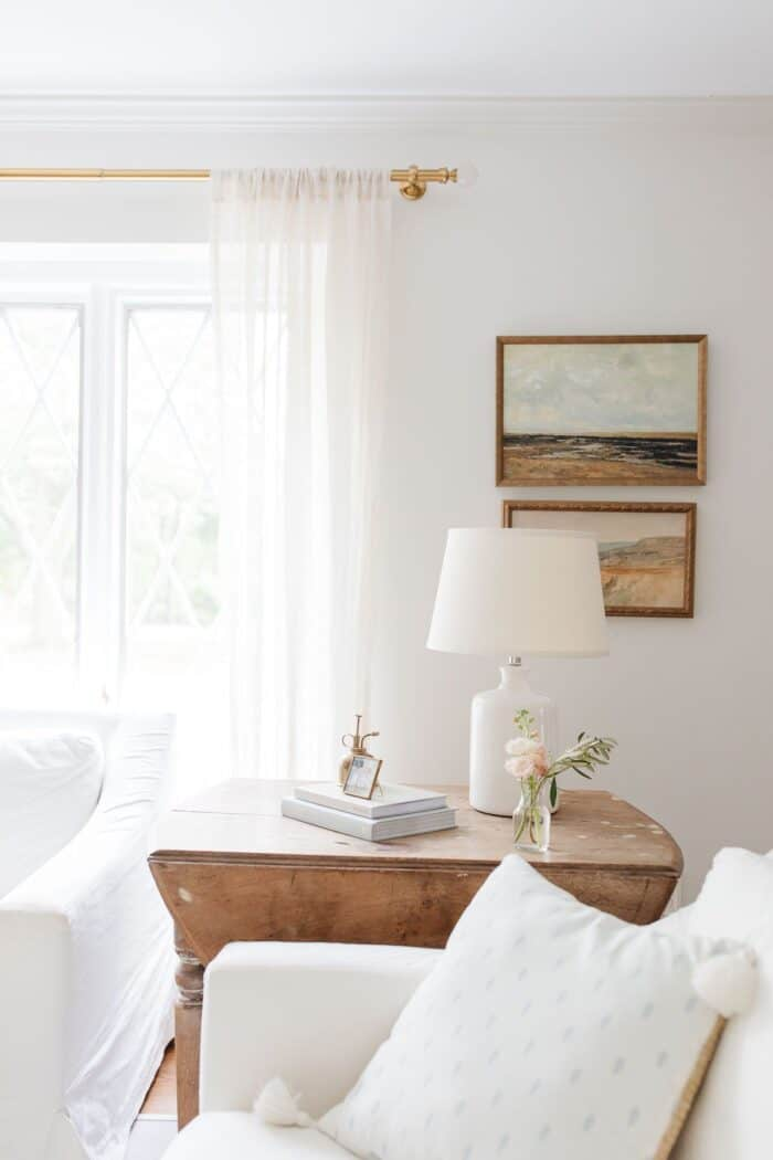 A white living room with neutral art and a wooden accent table.