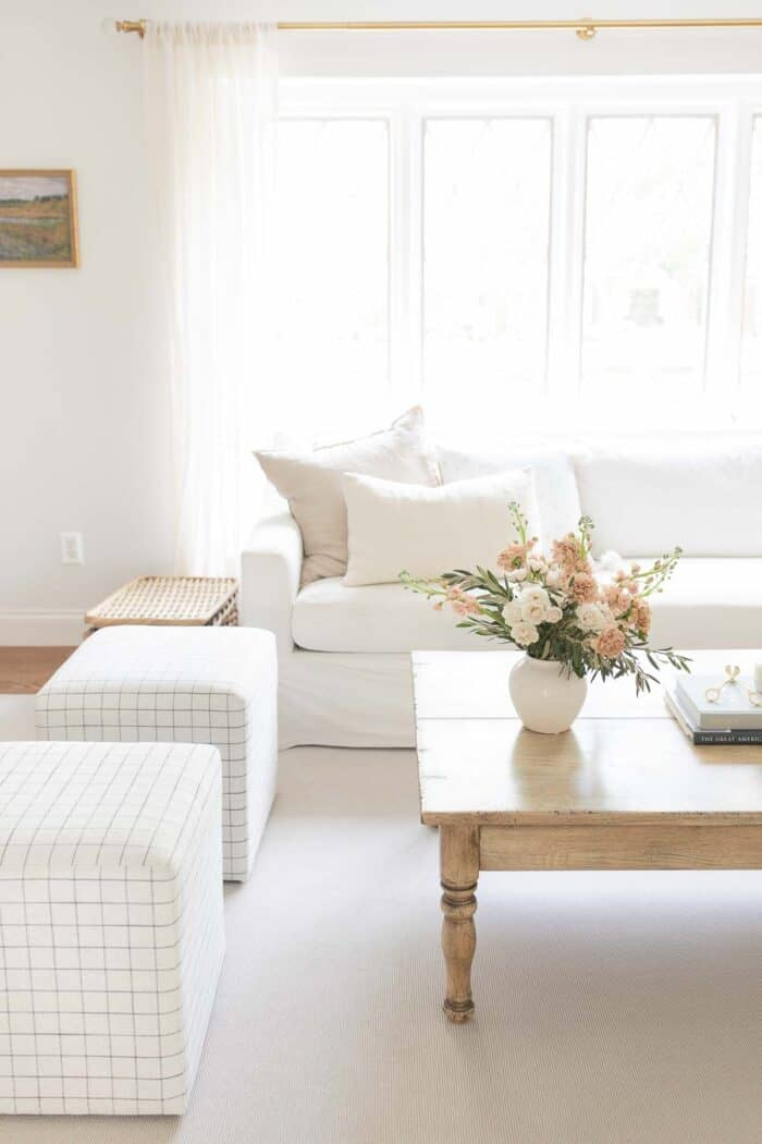 A white living room with a vase of flowers on the wood coffee table.