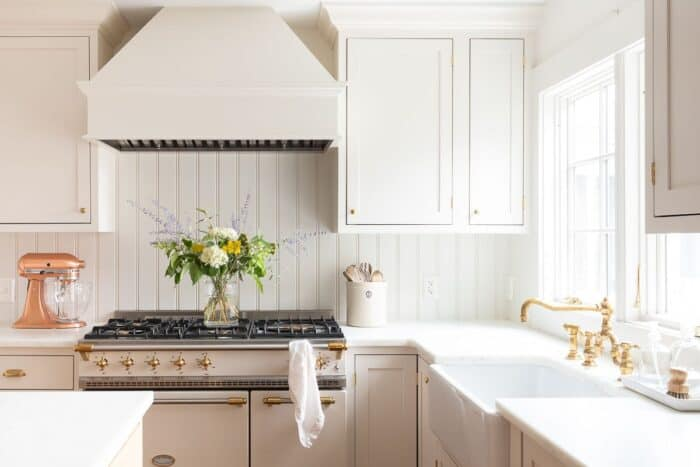 A cream kitchen with a vase of flowers on a french range.
