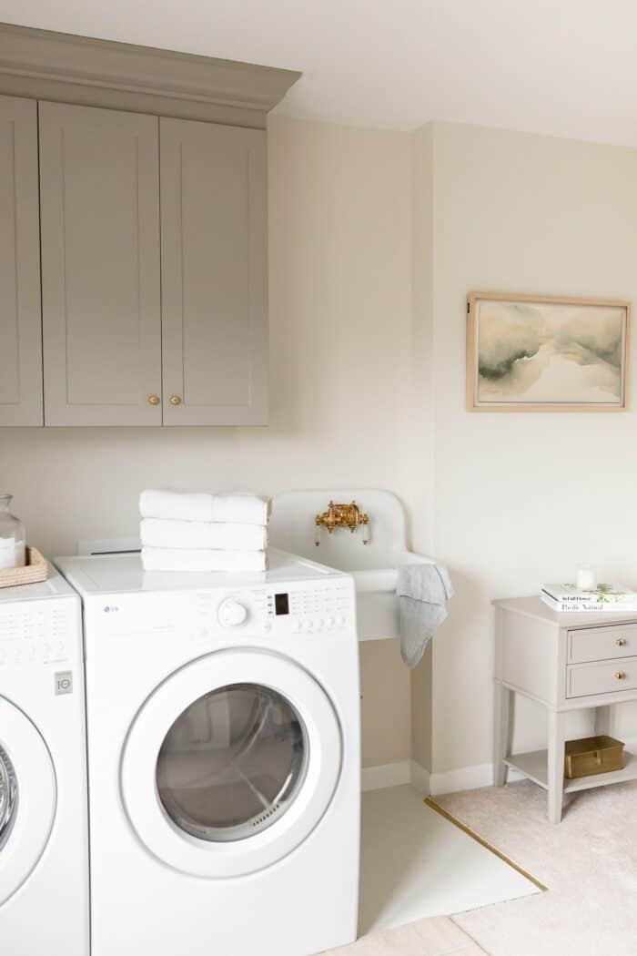 A laundry room with a small white sink and a side table and cabinets painted with furniture paint