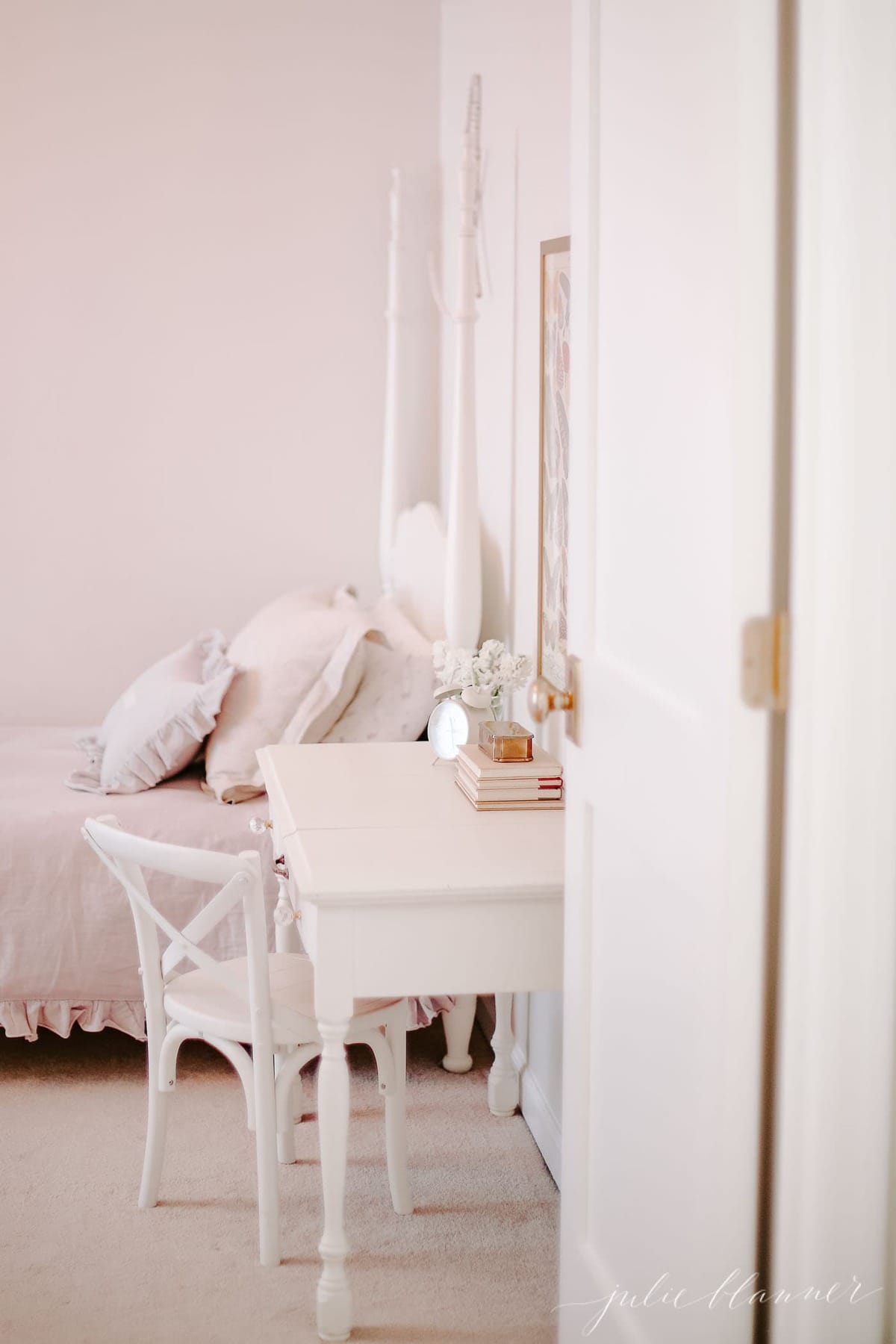A white little girl's bedroom with a bedside table painted in the best paint for furniture.