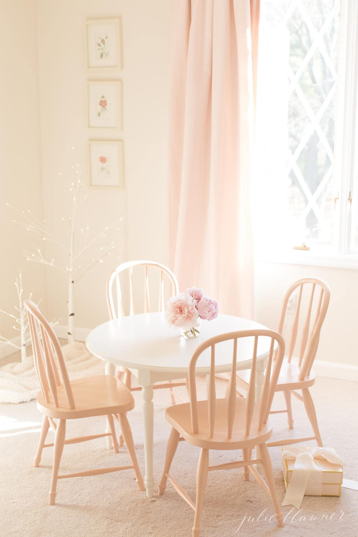 A white little girl's bedroom with a small round table and chairs painted in fresh furniture paint.