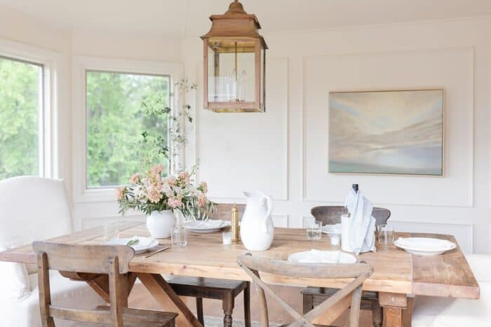 A farm table and chairs in a white dining room, brass lantern hanging above.