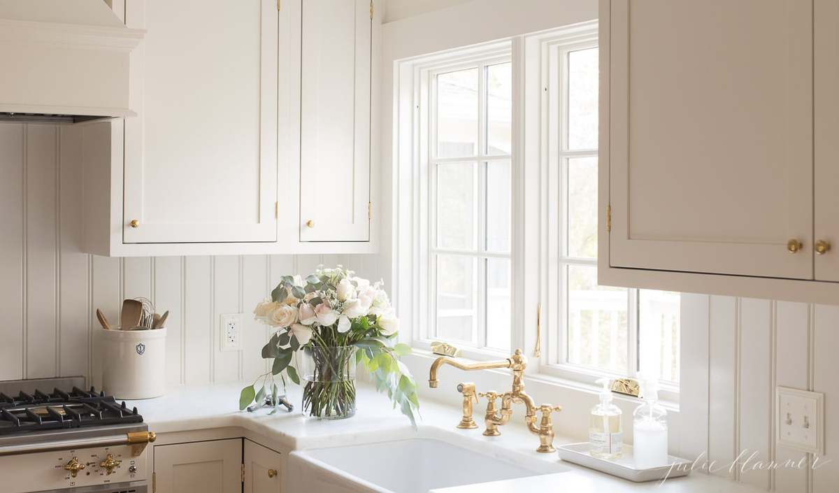 A white painted kitchen with a vase of flowers by the farm sink.