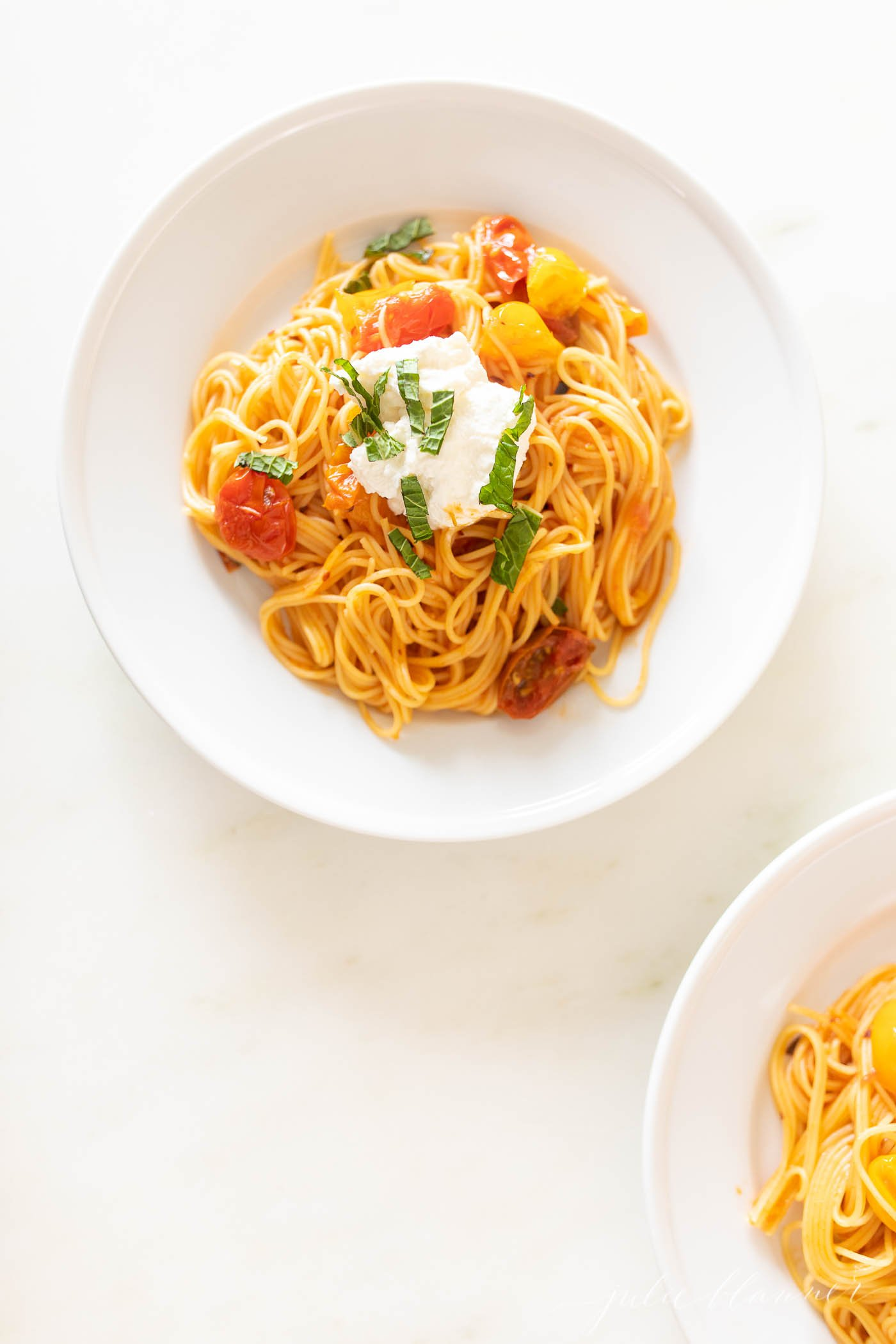 Cherry Tomato pasta on a white plate.