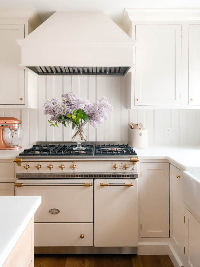 cream kitchen with lacanche range and lilacs