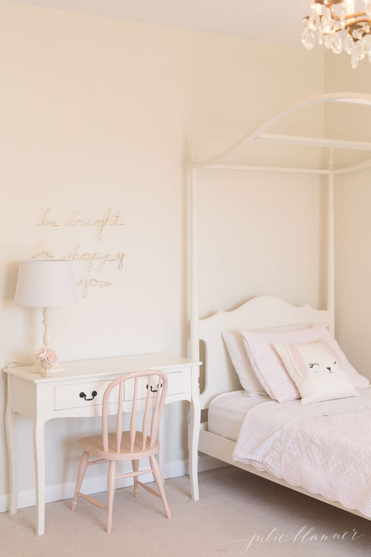 A white girls' bedroom and canopy bed with a bedside table painted with furniture paint.