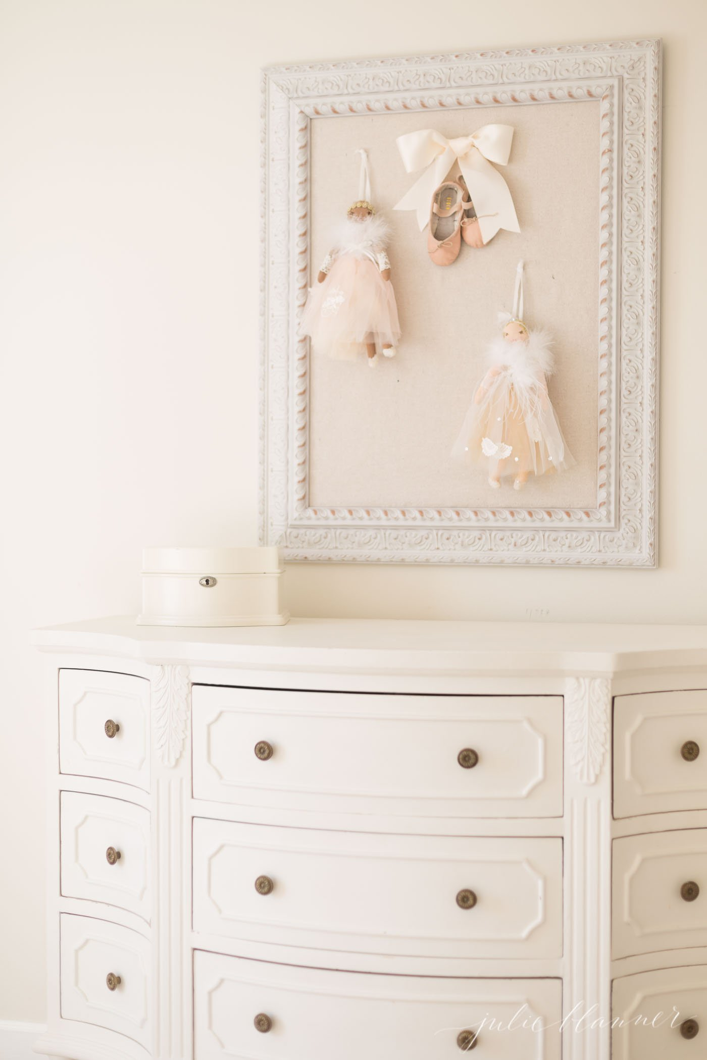 A little girl's bedroom scene with a white painted dresser and white pinboard with ballet details.