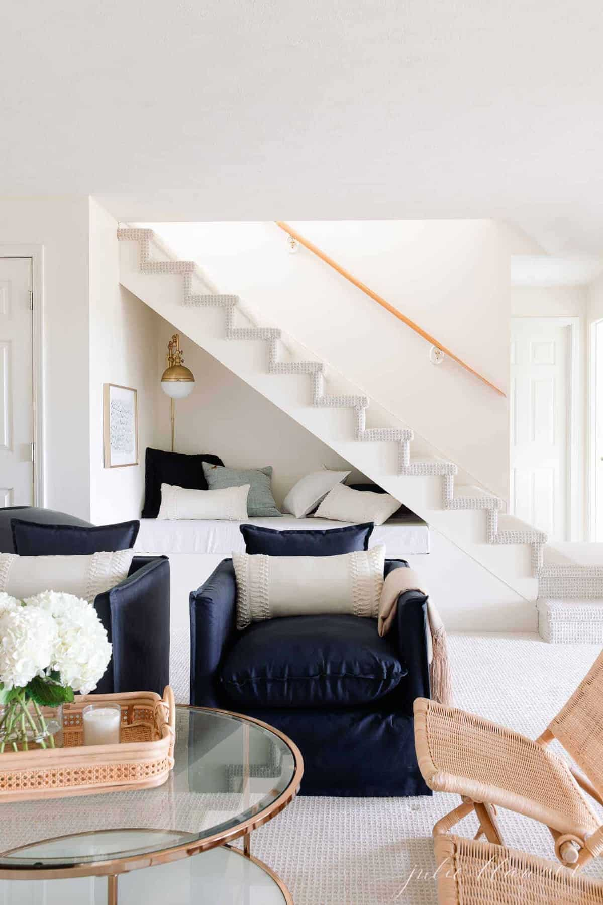 glass coffee table navy chairs and stair nook behind