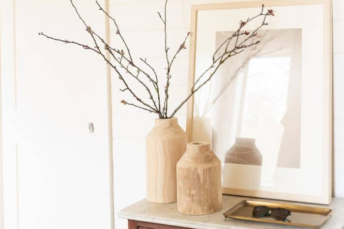 Wood vases on a vintage table in a white mudroom.