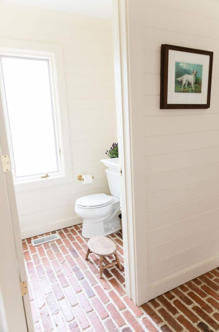 A guest bathroom with horizontal cedar paneling and brick floors.