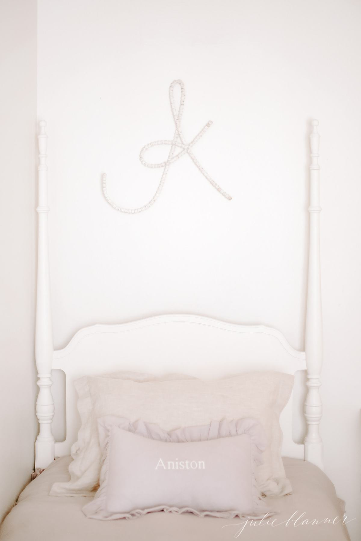 A white little girl's bedroom with a bed painted in furniture paint, and a large letter A over the bed.