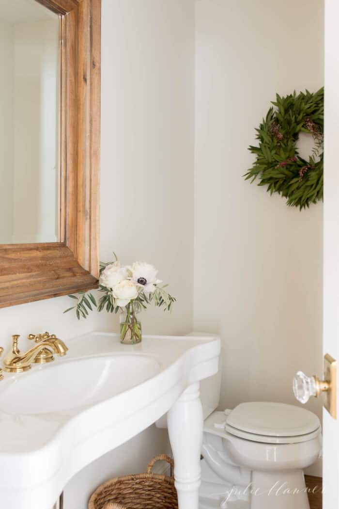 powder room with white parisian sink and wood mirror