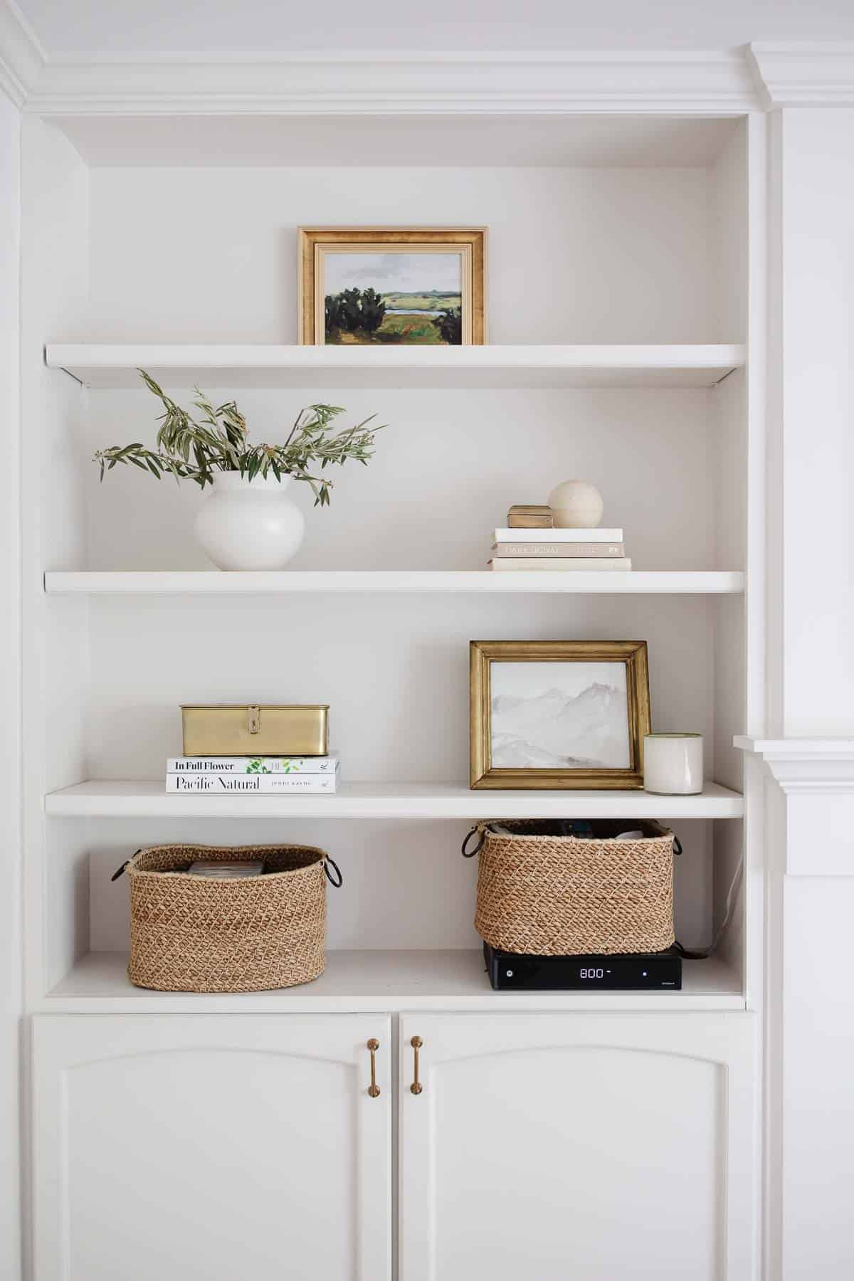 Built in bookcases with minimal baskets paintings and accessories