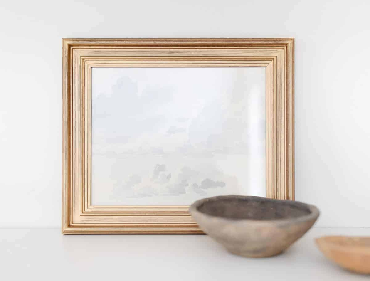 watercolor in gold frame with pottery in front
