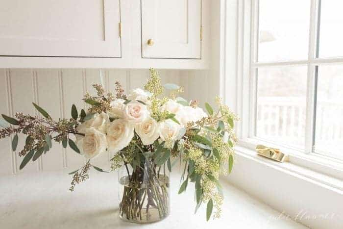 A vase arrangement of white trader joes flowers in a white kitchen